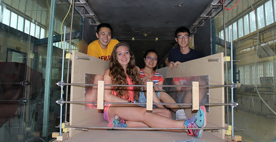 "Andrew Wang, Amber Phillps, HongXiang ""Nicole"" Yue from Lanzhou University and Dan Gil pose inside the structure they built to test electrostatic charging inside the wind tunnel."