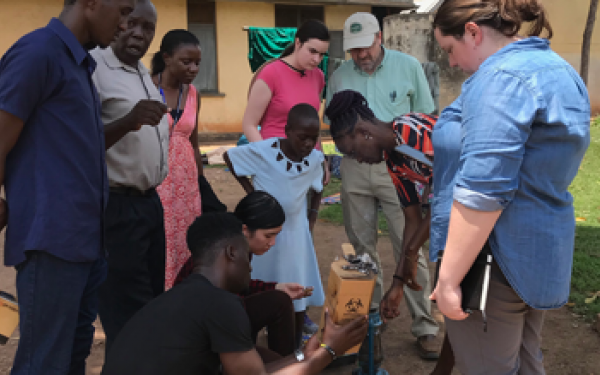 Team of students and faculty gather around a syringe and needle disposal system prototype