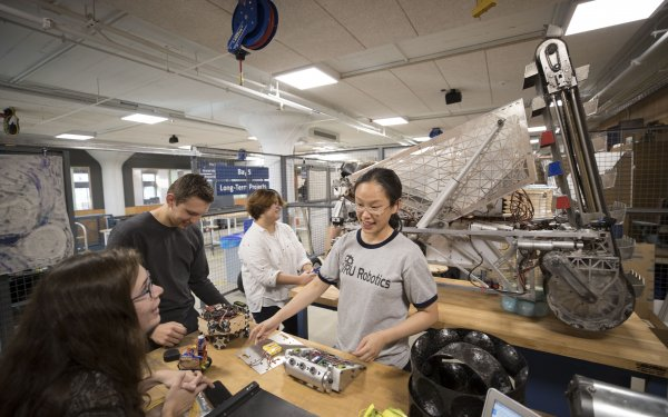 Four member of the robotics team work in their bay