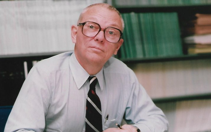 Lucien A. Schmit, Jr. sitting at his office desk