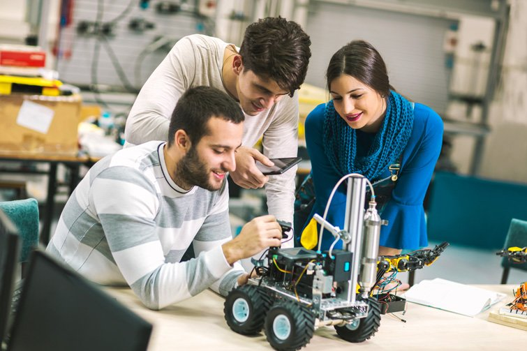 Engineering students working on a robotics project in a lab