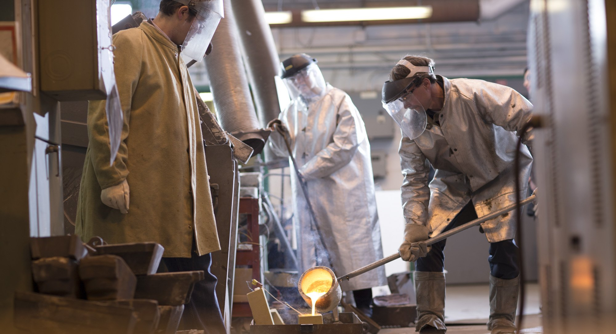 materials students and professor pouring a cast in the Metal Processing Lab