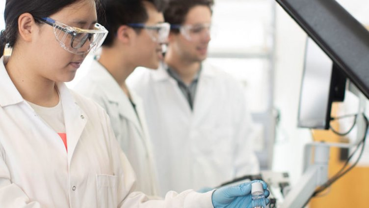 three students in lab coats