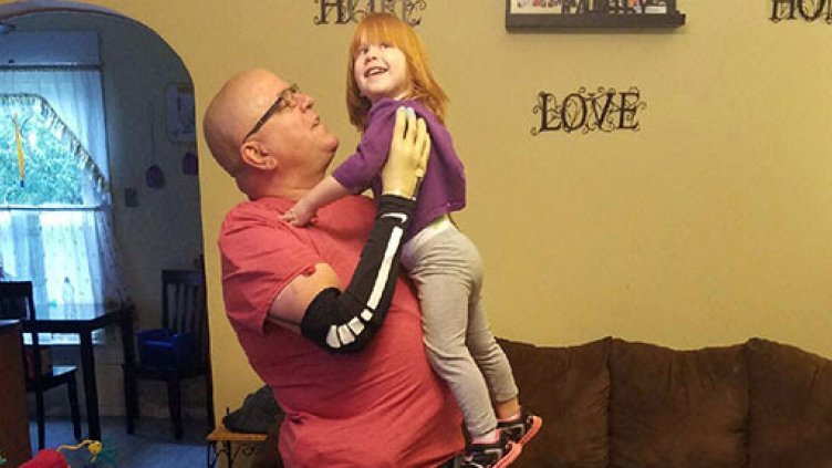 Keith Vonderheuvel lifting granddaughter while using sensory enabled prosthetic hand