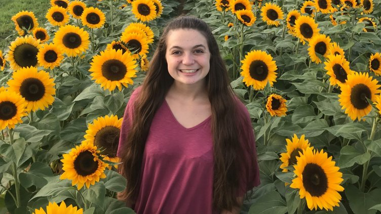 Headshot of Alex Welsh in a sunflower field