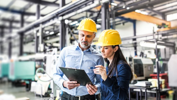 two engineers in hard hats review checklist