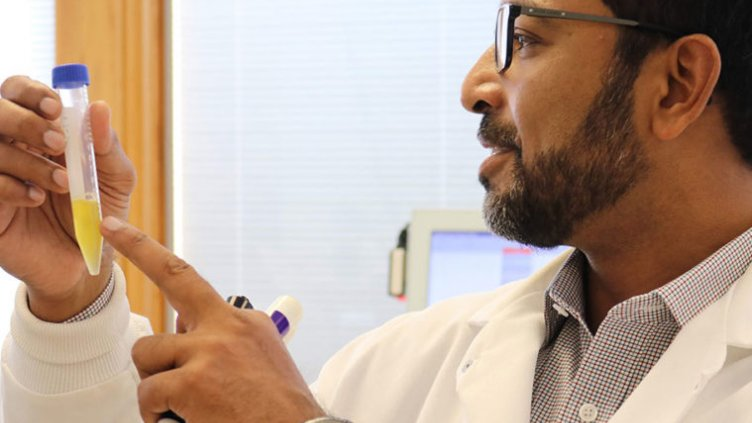 anirban sen gupta looking at vial of platelets