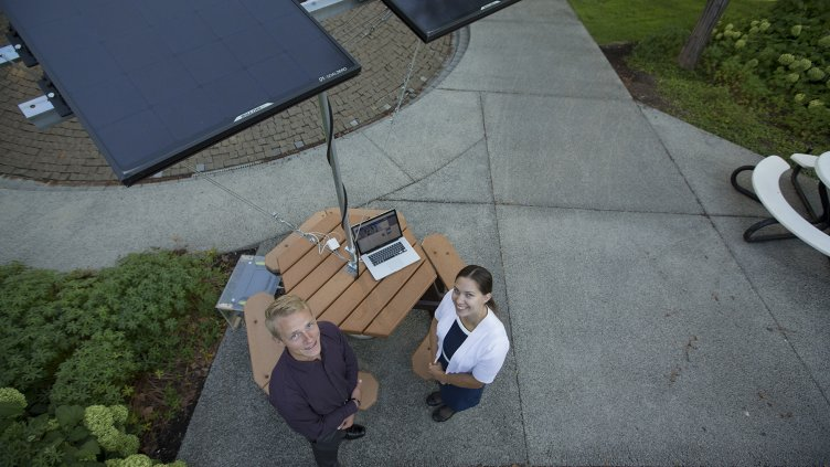 Jason Pickering and Elizabeth Freud with solar charging picnic table