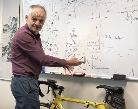 Professor Dominique Durand standing in front of his bike and a white board