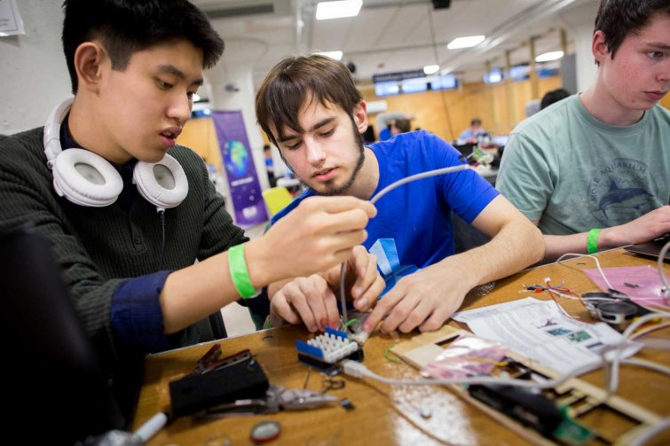 Three students work on electronics at HackCWRU 2015