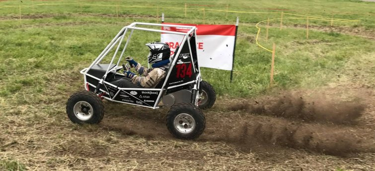Baja SAE student team member driving car on a course