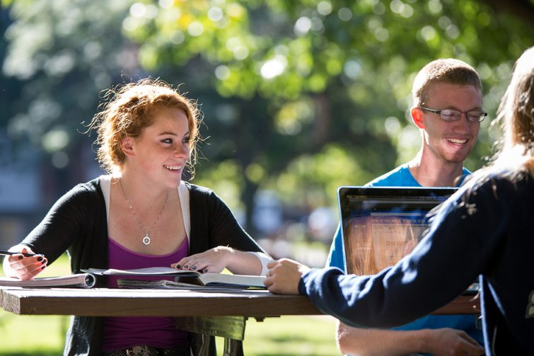 students on campus quad studying at picnic table