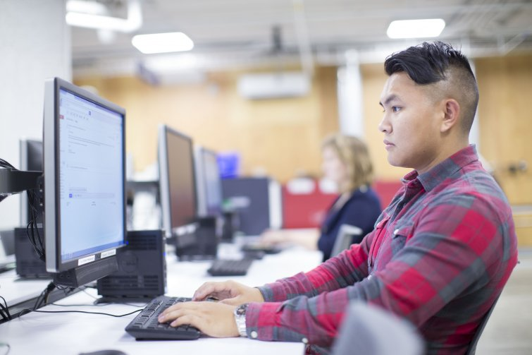 A student working at a computer terminal in think[box]