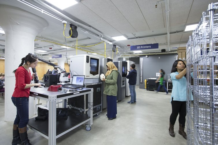 Four students working near the 3D printers in think[box]