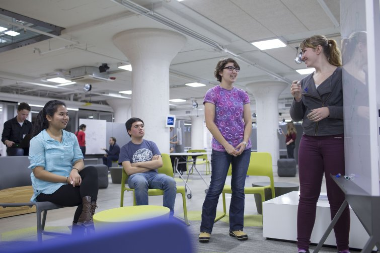 Four students holding a meeting in front of a whiteboard