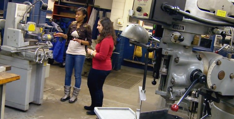 two mechanical engineering women students talking in the metal shop