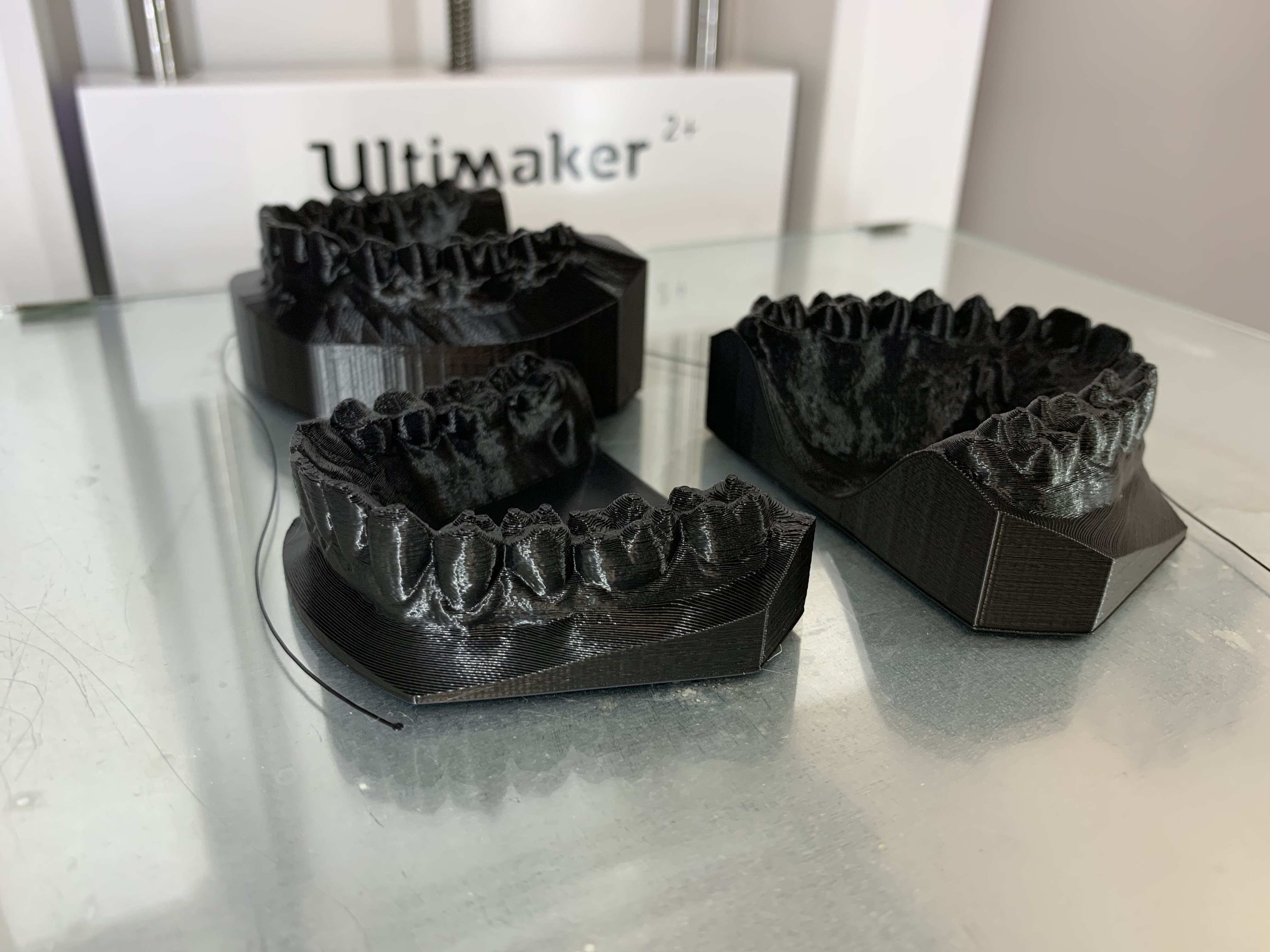 Three sets of black plastic teeth sit on a 3d print build plate.