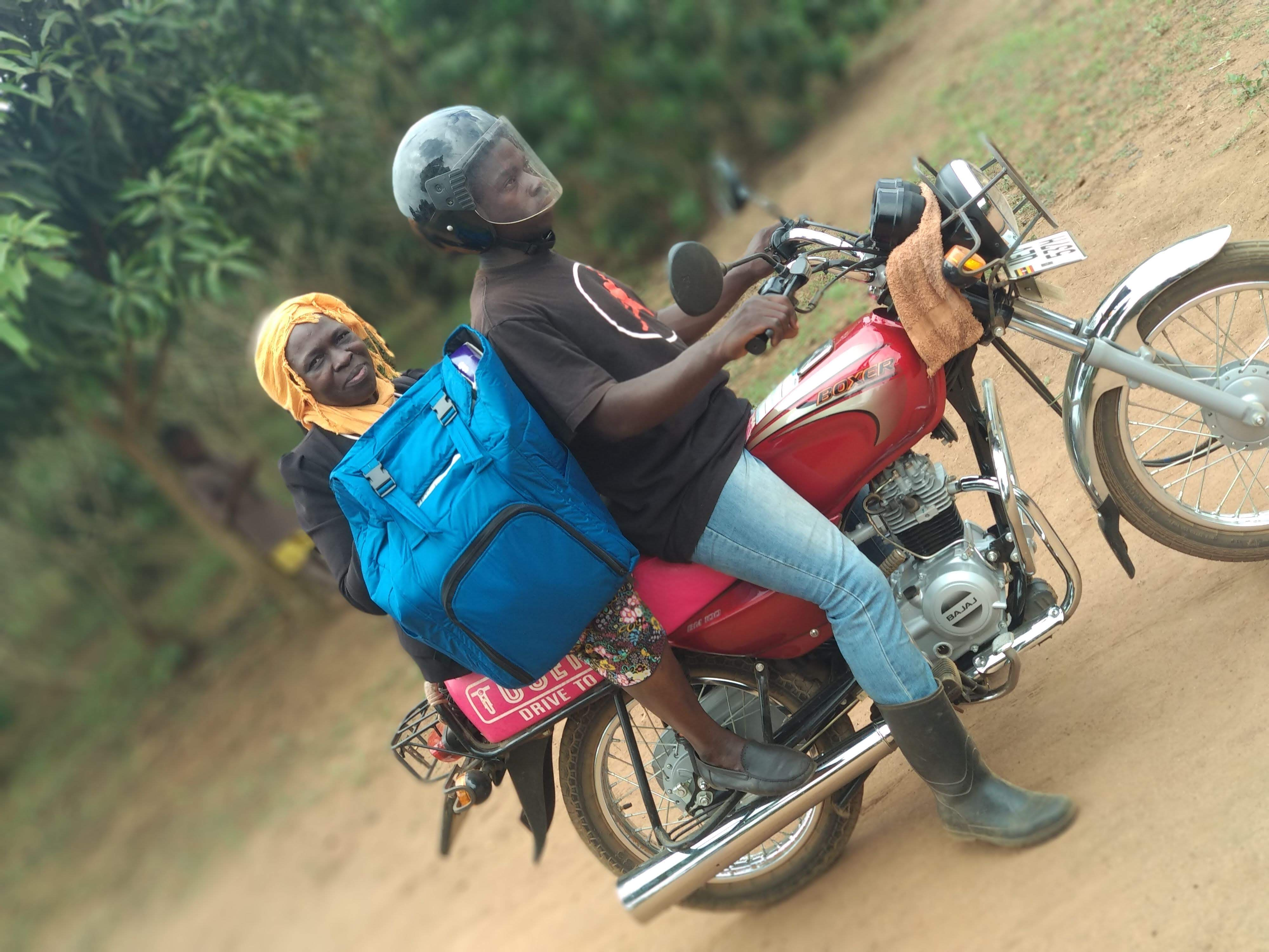 An African man and woman sit on a red motorcycle. the woman is carrying a blue backpack design to carry vaccines over long distances.