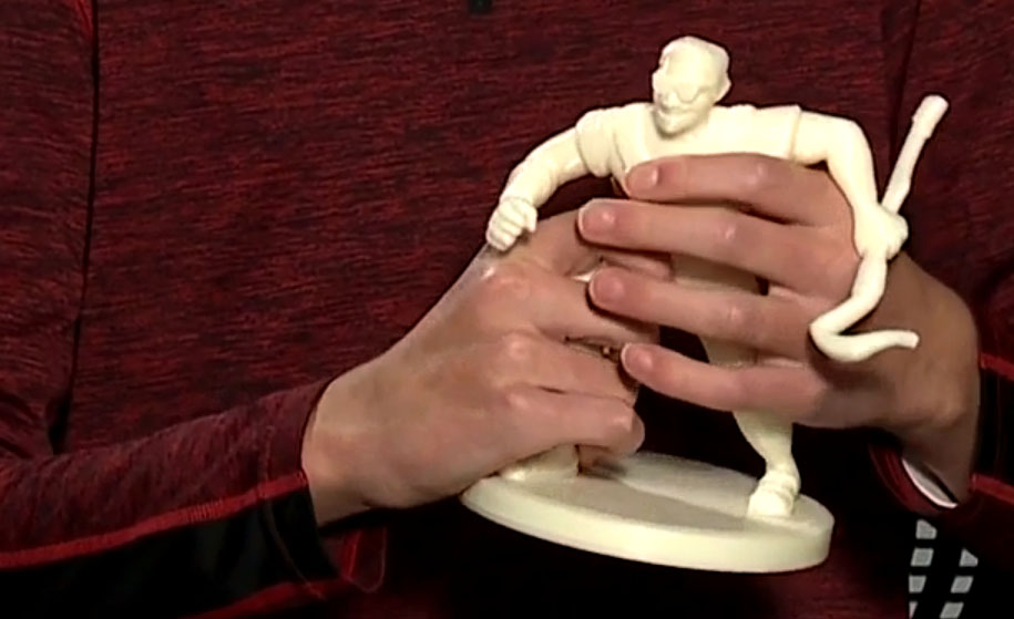 a young man holds a 3D printed superhero figurine