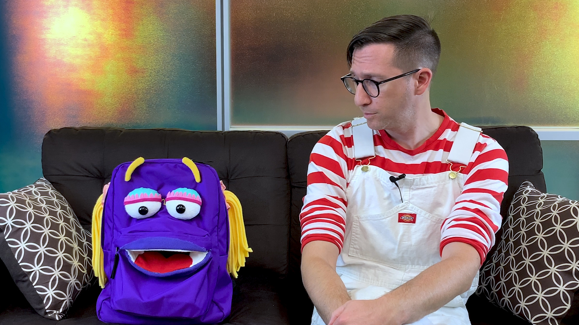 Jan the Backpack, an electronic puppet, sits on a couch next to creator Ian Charnas.