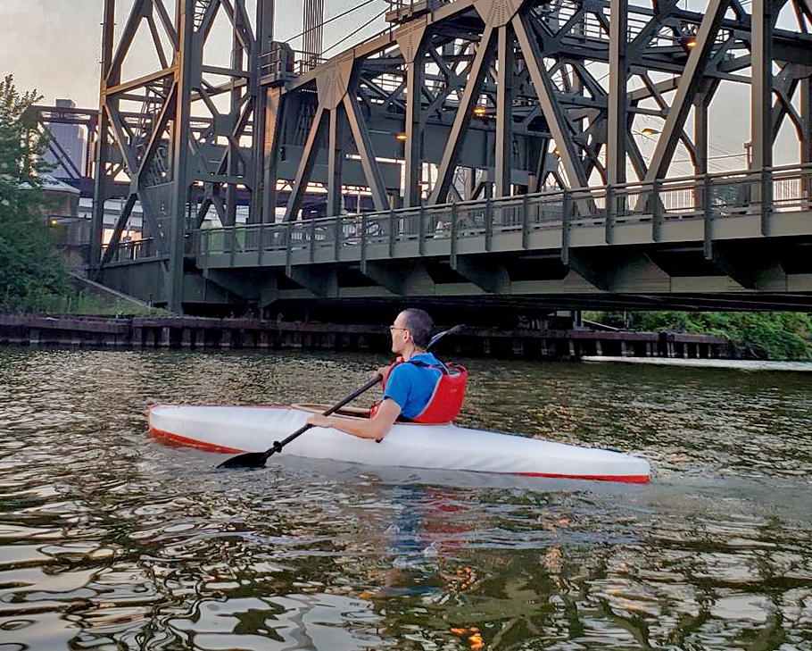 A handmade skin on frame kayak is piloted down the Cuyahoga River by creator Umit Erol.