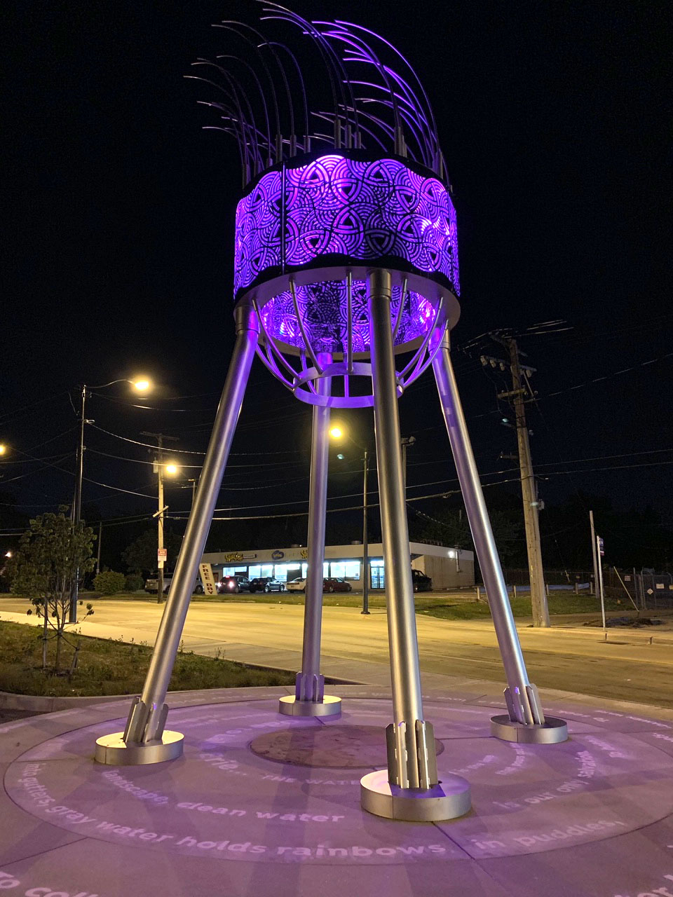 an illuminated water tower made from stainless steel above a poem inscribed on the pavement